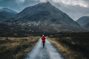 Woman walking on a road in Glen Etive, Scotland